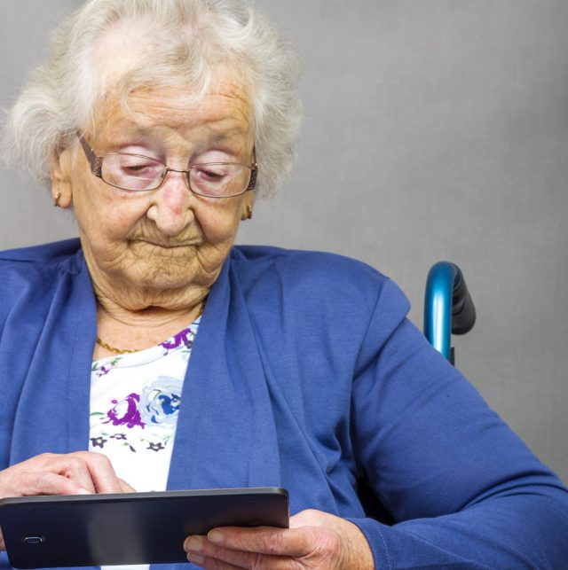 Disabled Senior citizen using a computer tablet.