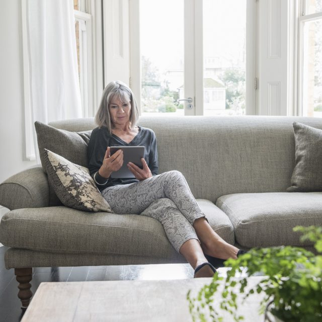 Woman in her 60s at home using a tablet. She is sitting on a grey sofa in front of a window in the living room, an dis comfortable and relaxed.