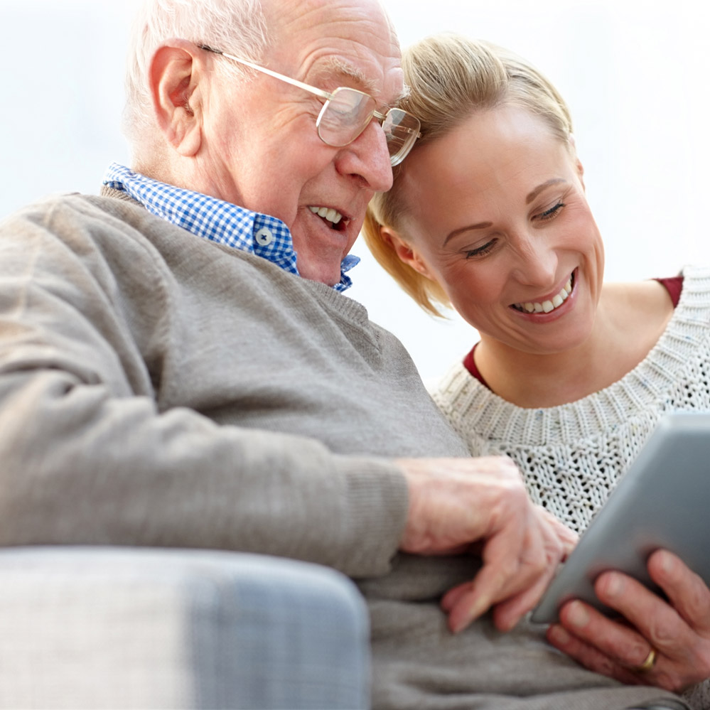 Happy father and daughter sitting on sofa using digital tablet - Indoors